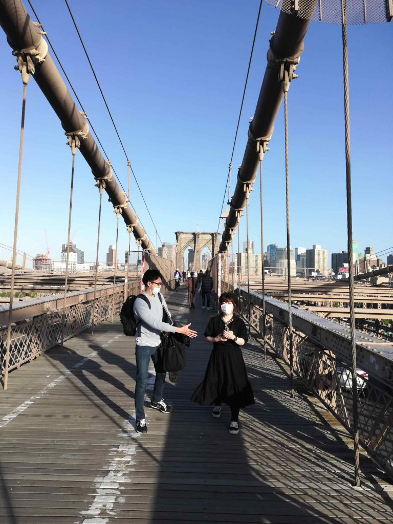 couple with masks crossing the Brooklyn bridge