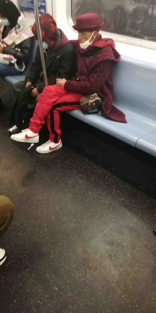 MTA Subway passenger wearing red and mask on chin