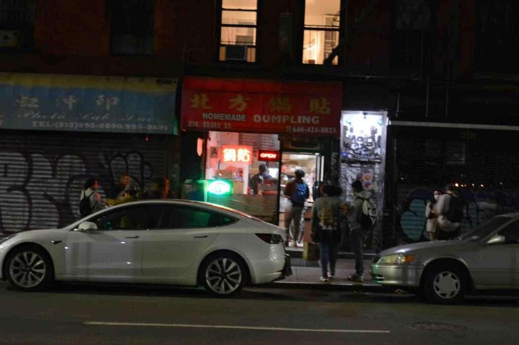 NYC night photography people buying dumplings